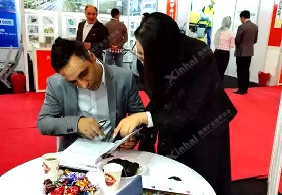 展会上,鑫海伊朗负责人曲春蕾女士正在为中东的客商介绍鑫海EPC项目的服务细节。